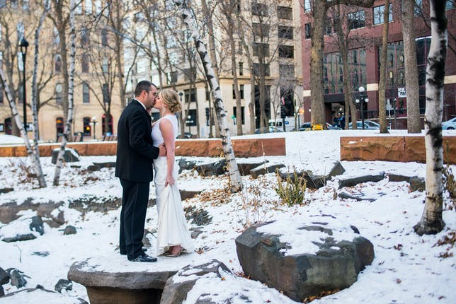 venue exterior space in winter with couple kissing in snow on a rock