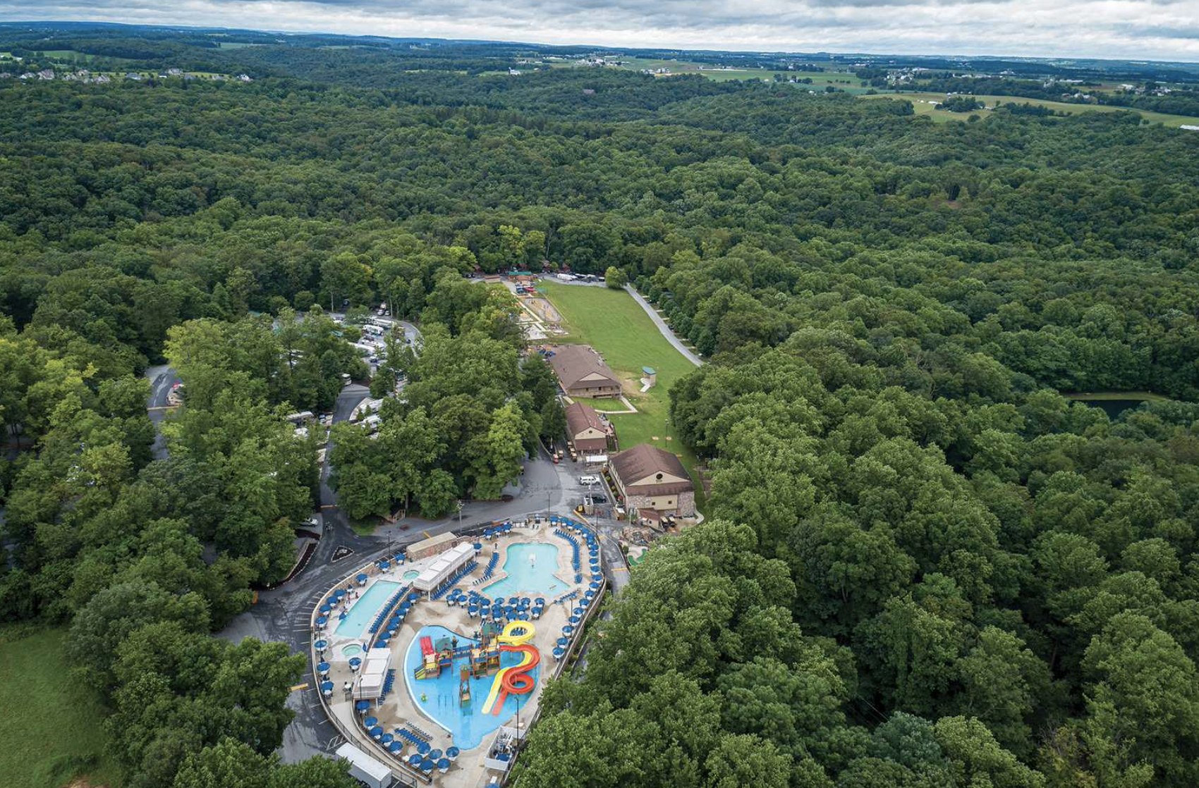 Aerial view of campground in the woods with pool area