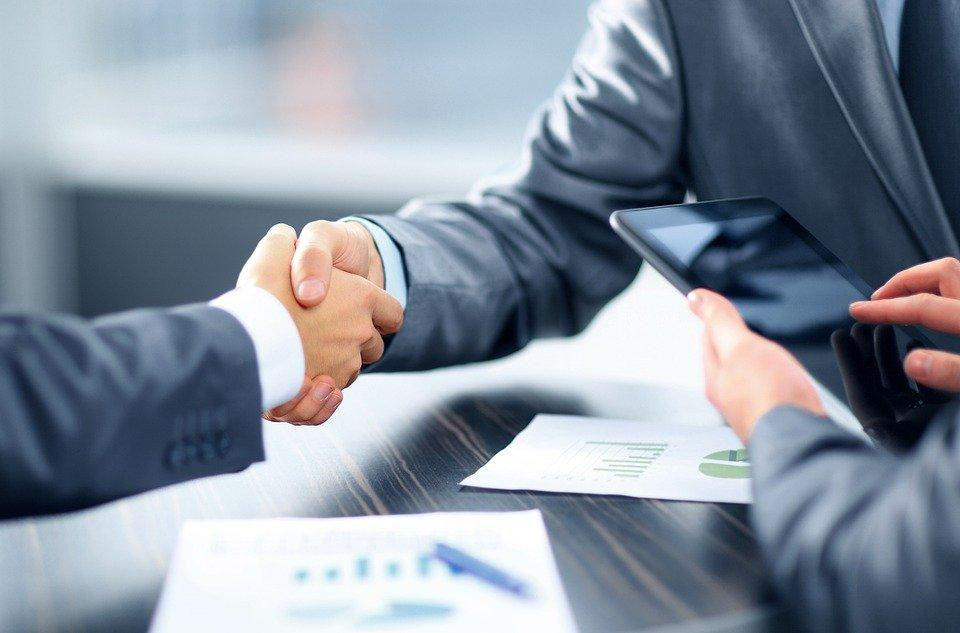 Two men shaking hands during a loan application process