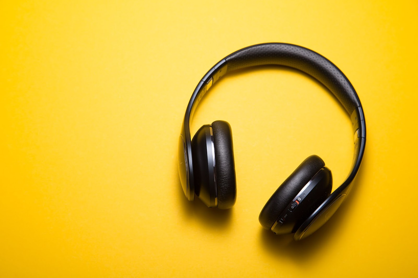 Photo of headphones on yellow background to represent a roundup of the best headphones for video editing.