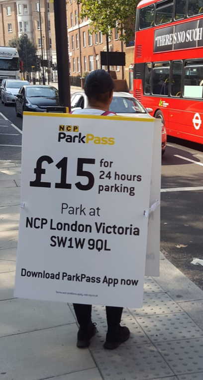 A person holding a sign  Description automatically generated with medium confidence