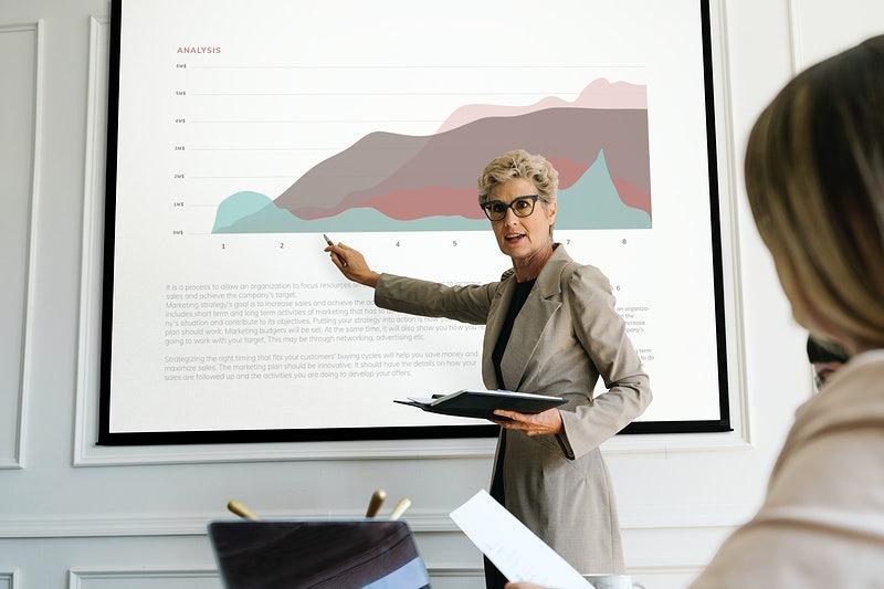 Uma mulher apontando para uma apresentação com um gráfico.