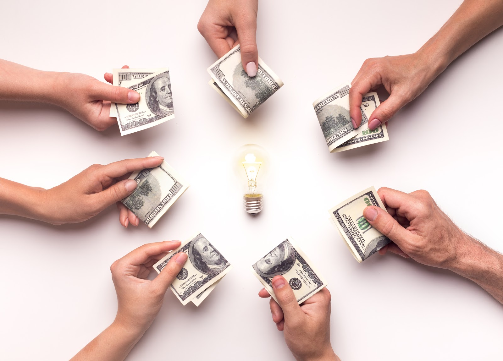 How often are dividends paid: Hands hold money in a circle around a light bulb