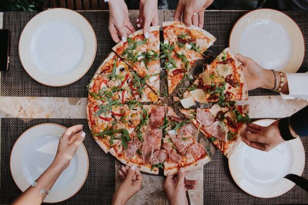 Foto tirada de cima de uma pizza com mãos pegando os pedaços