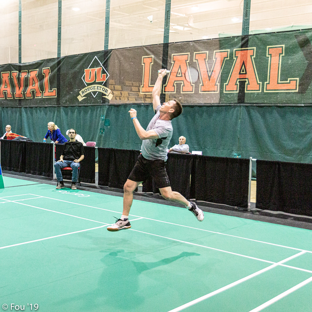 A man has his eyes on a shuttlecock up above him.  He is in the rear of his court, with both feet off of the surface.  He is prepared to connect for what could be a highly accurate badminton jump smash.