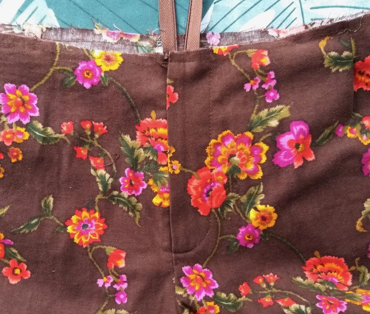 A fly front in a trouser sewn up in 70s style brown floral textured fabric. The waist is unfinished.