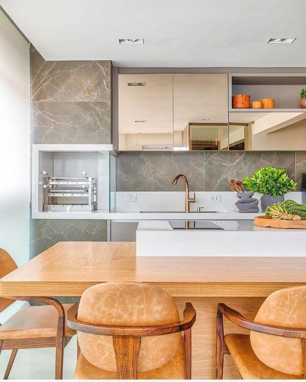 Cozinha gourmet com churrasqueira e parede da pia revestidas de porcelanato reproduzindo mármore cinza, bancadas brancas, mesa de madeira com cadeiras de madeiras, armários espelhados e piso branco.
