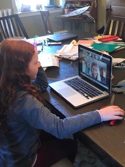 Holy Cross student attends class remotely using school-supplied Chromebook.