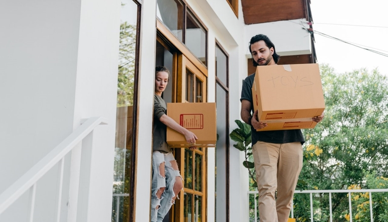 A couple carrying moving boxes out to their moving truck or portable container.