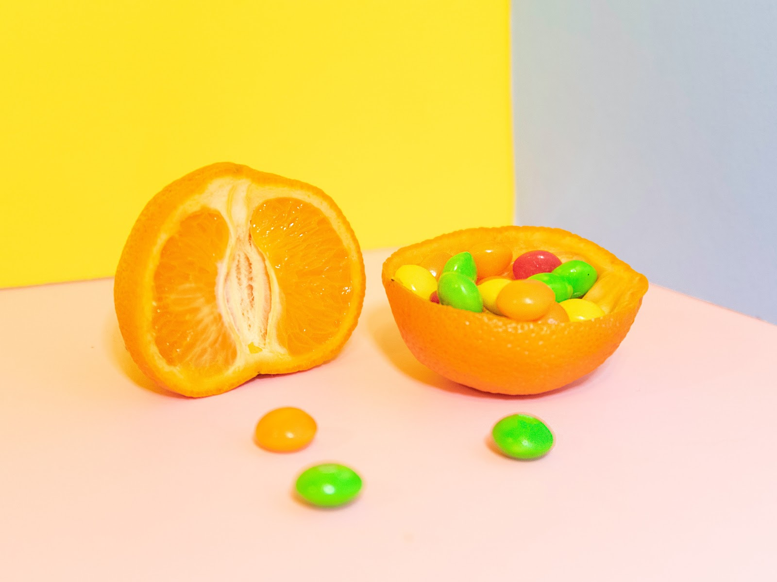 Orange cut in half. One side is filled with candy. On a tri-color muted color backdrop: yellow, pink, and blue.