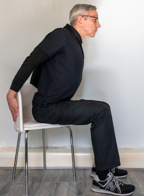 instructor seated with hands behind the chair, stretching his chest muscles