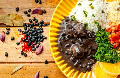 Top view arrangement of tasty black bean stew served on yellow plate with rice and couscous topped with cut tomatoes and parsley
