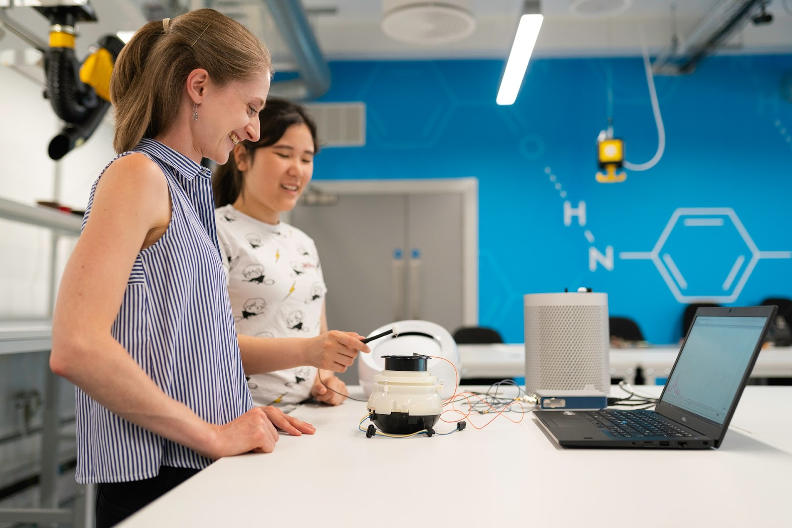 Two young girls stand in a <mark><mark><mark>STEM classroom</mark></mark></mark> in front of a white table smiling as they code a <mark><mark><mark>robot</mark></mark></mark> with a laptop.