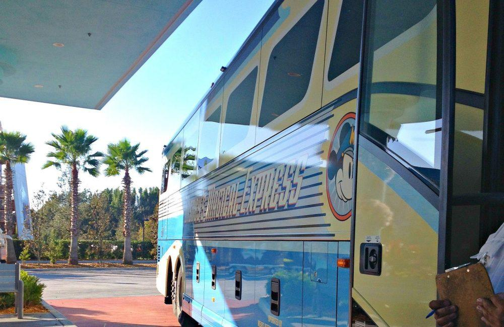 Magical Express Disney bus is yellow and blue with Mickey Mouse on the site of it.