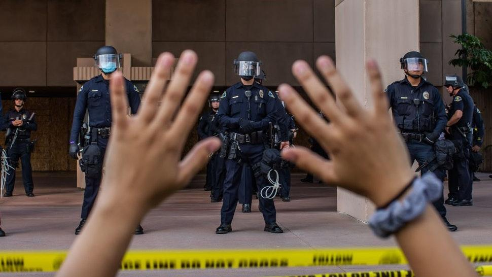 A demonstrator holds her hands up while she kneels in front of the Police at the Anaheim City Hall on June 1, 2020 in Anaheim, California, during a peaceful protest over the death of George Floyd. - Major US cities -- convulsed by protests, clashes with police and looting since the death in Minneapolis police custody of George Floyd a week ago -- braced Monday for another night of unrest. More than 40 cities have imposed curfews after consecutive nights of tension that included looting and the trashing of parked cars.