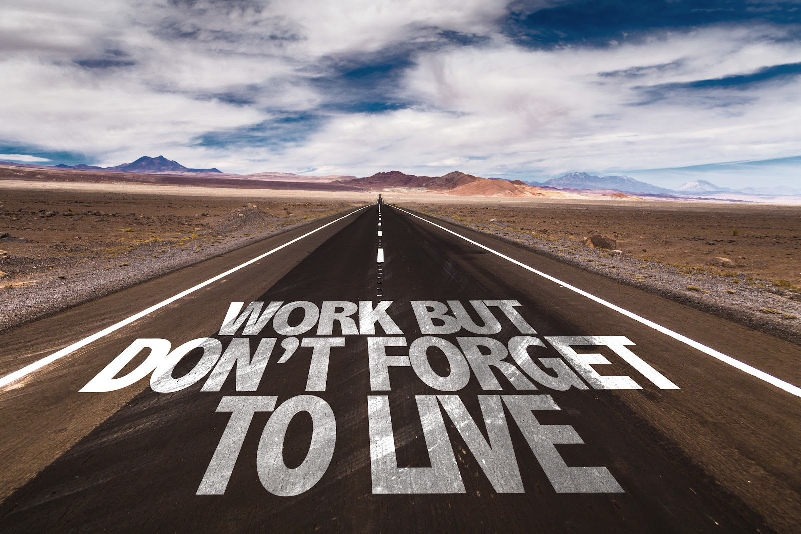 """Long desert road painted with """"work but don't forget to live"""""""