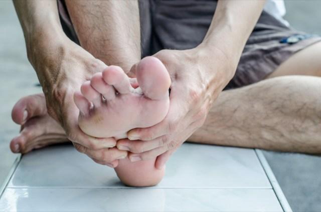 Man's hand being massaged a foot