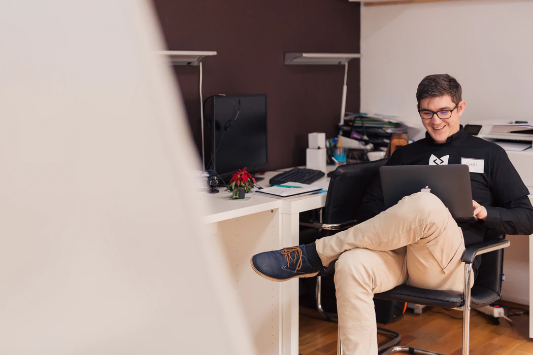a young male adult sitting inside an office, with his laptop on his lap. He wears black-framed glasses, a black hoodie with a white logo on the front, khaki pants, and blue shoes with brown laces. He looks happy.
