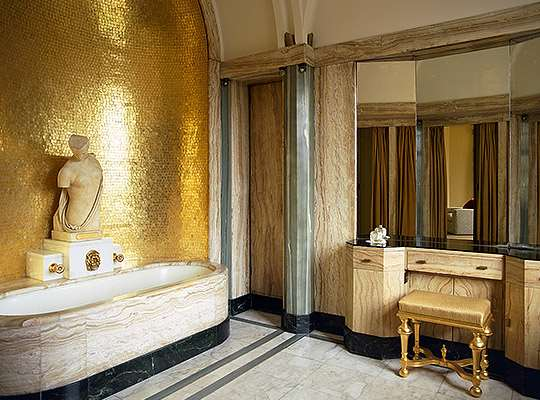 Virginia Courtauld's bathroom, one of many original interiors to survive from the 1930s. The walls are lined with onyx, with gold mosaic tiles in the bath niche