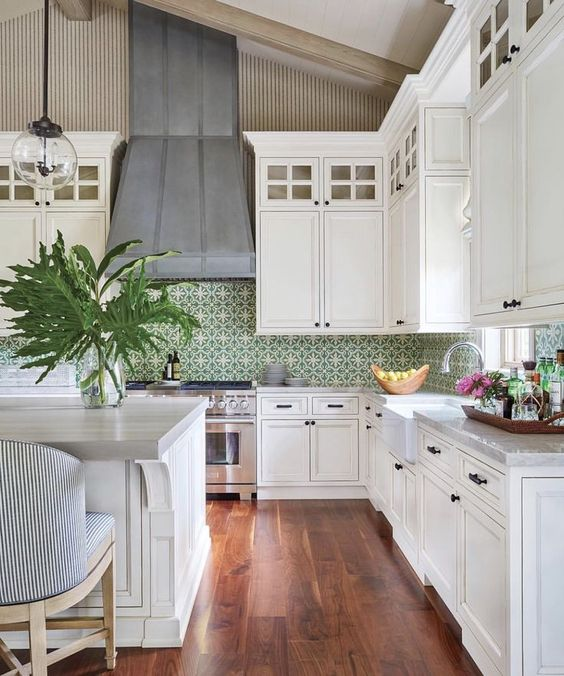 large farmhouse kitchen with white shaker cabinets, green patterned tile backsplash, oversized center island, black cabinet hardware, glass globe pendant lights and large steel range hood