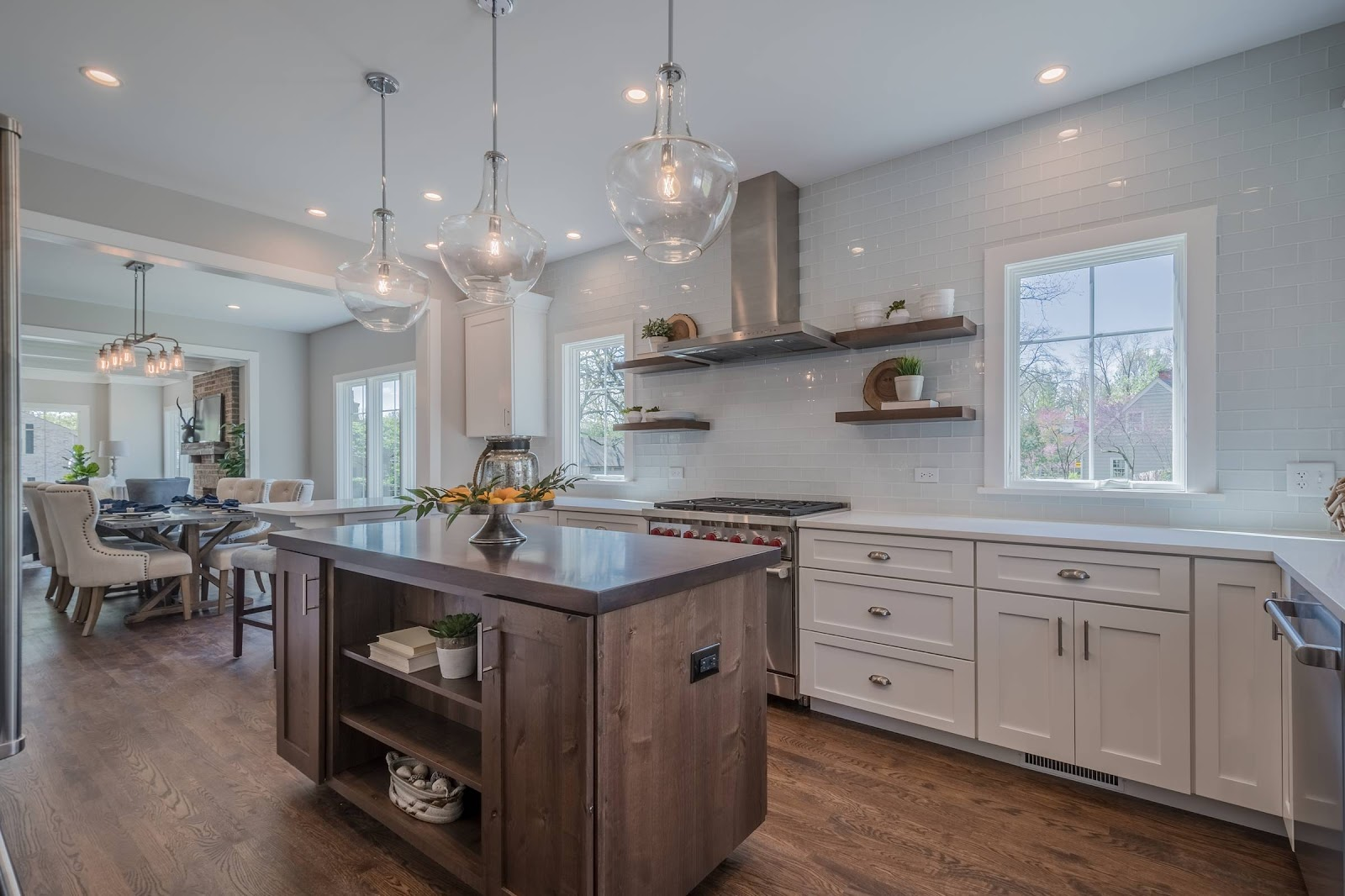 Natural wood island contrasts and all white kitchen. Multiple windows and glass pendants provide ample, inviting light to the open floor plan leading to the dining and living room spaces.
