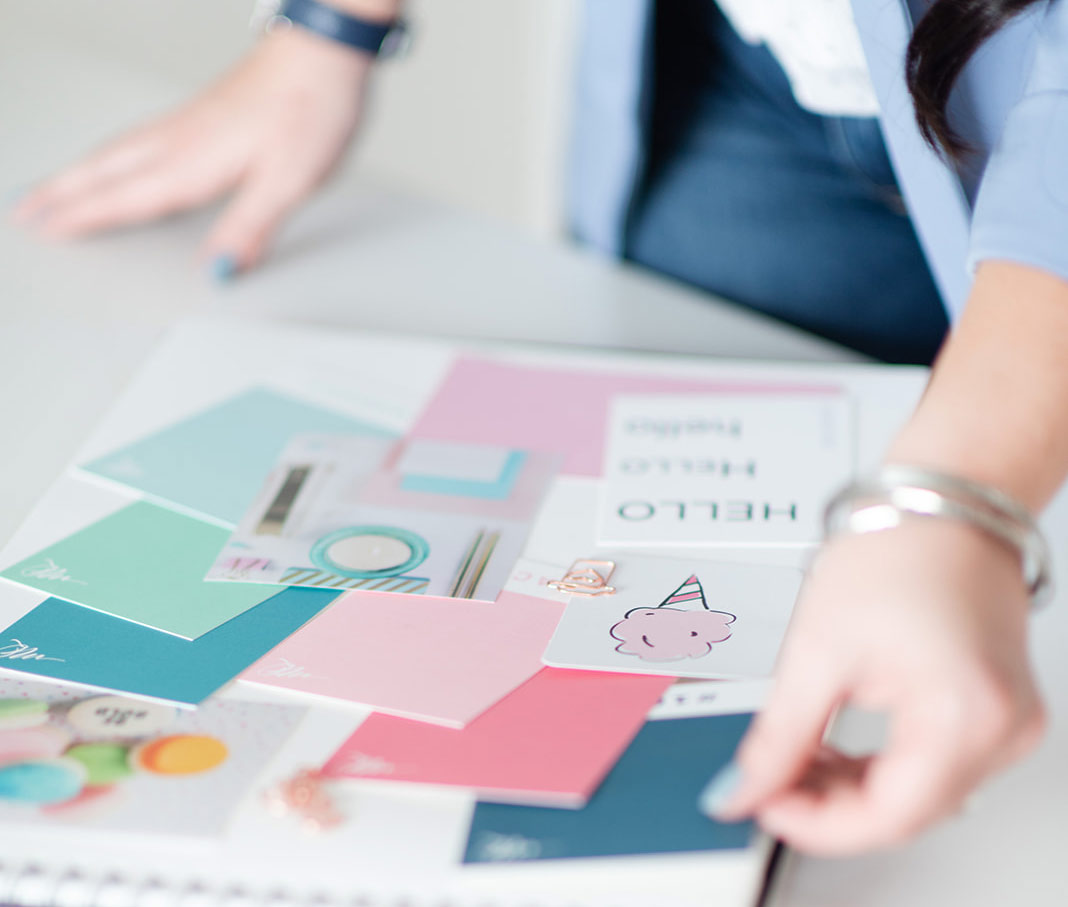 A woman looking at color swatches and font type examples of a branding kit on a tabletop.