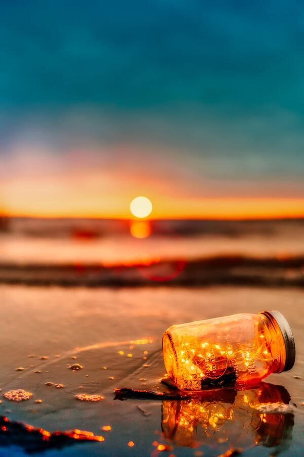 pote de vidro quebrado com luzes dentro na areia da praia