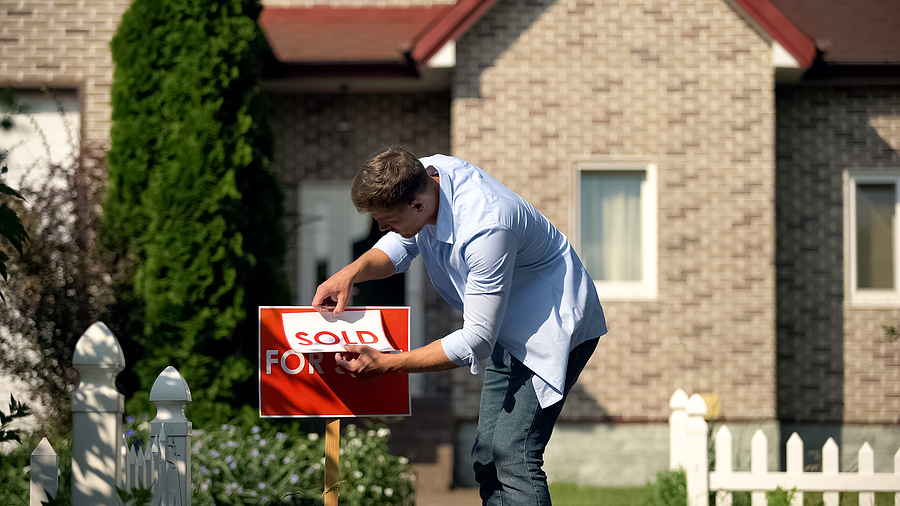 """FSBO home seller putting """"sold"""" sign over his for sale sign after a successful sale at the right price"""