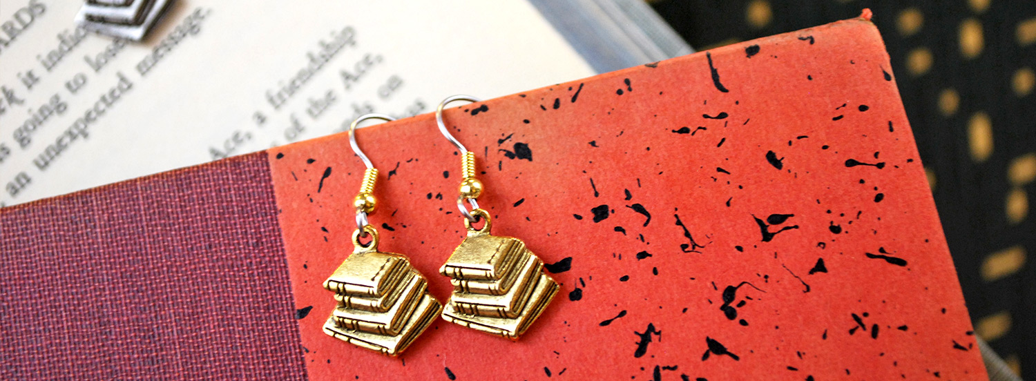 A pair of gold-colored earrings, each with a charm of a stack of books