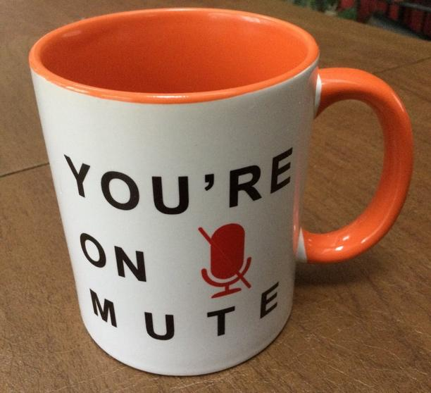 """A white coffee mug with an orange handle, with the all caps text """"YOU'RE ON MUTE"""" and a red microphone icon with a slash through it"""