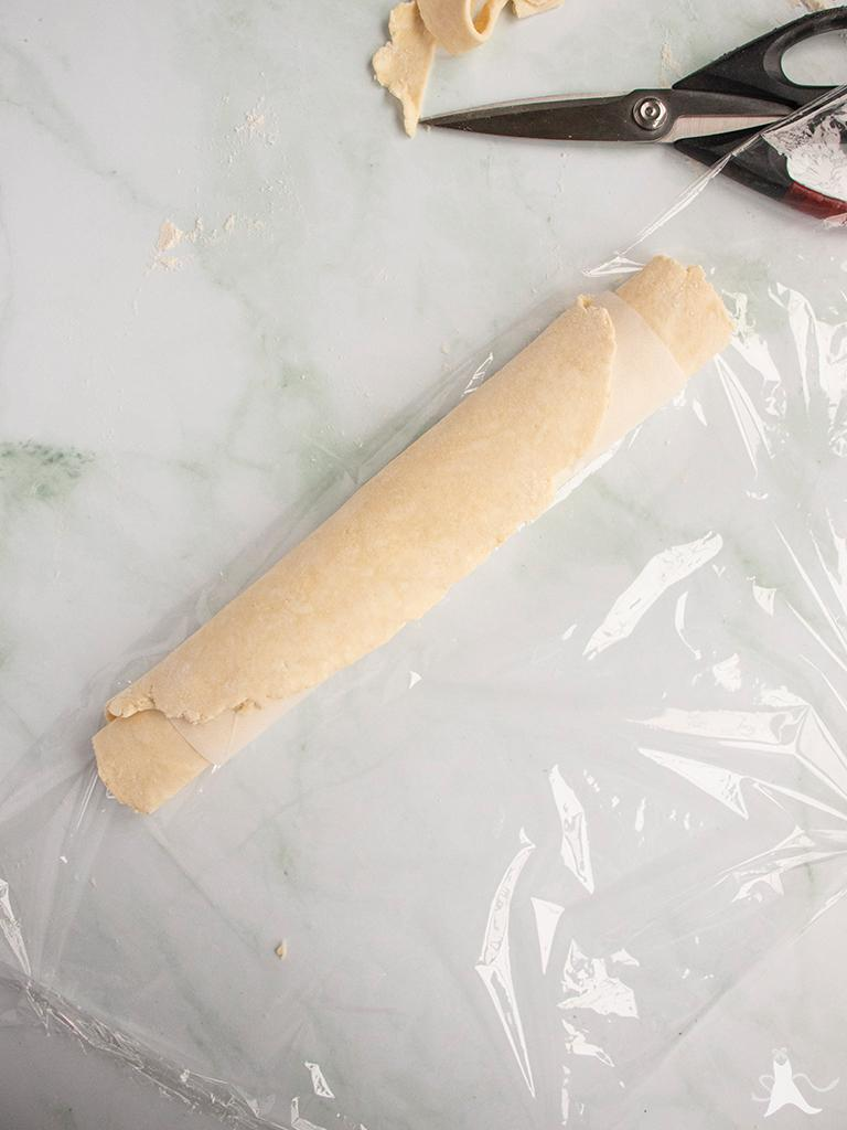 Pie crust dough rolled in parchment ready to freeze for later