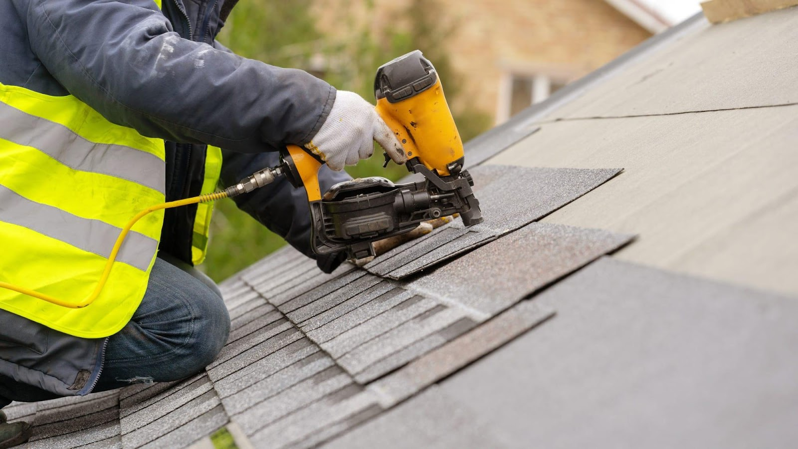 Workman using pneumatic nail gun install tile on roof of new house under  construction - Shingle Tech