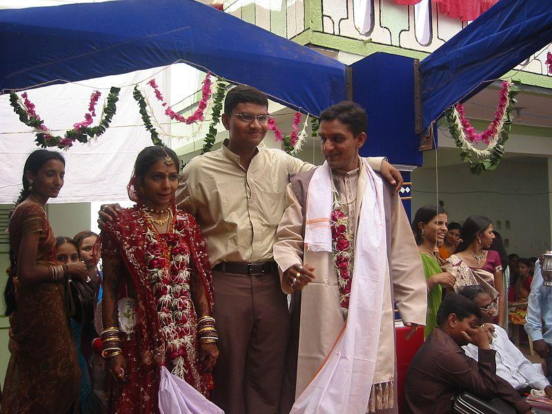 An indian wedding. The bride and groom are standing near each other and a long, white sash from the woman's gown is wrapped around the man's shoulders.