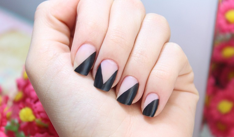 Mão com unhas pintadas de bege com desenhos diagonais em preto. Foto: Site Jana Taffarel. Post: Nail art fáceis para fazer em casa