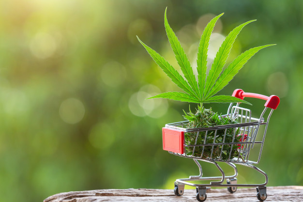An image showing you the concept of buying cannabis on a shopping trolley.