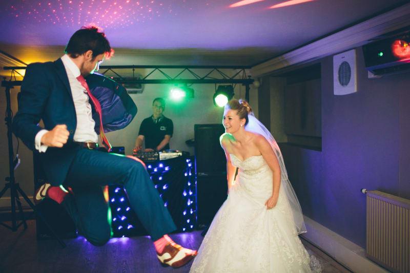 Bridebook.co.uk- groom jumps on dance floor as bride laughs