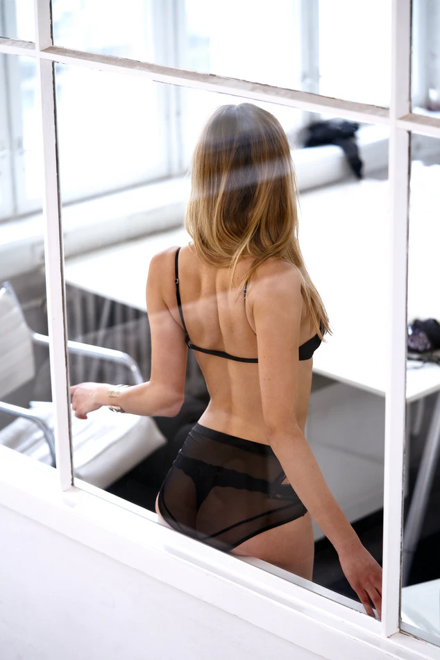 woman wearing lingerie with back against window