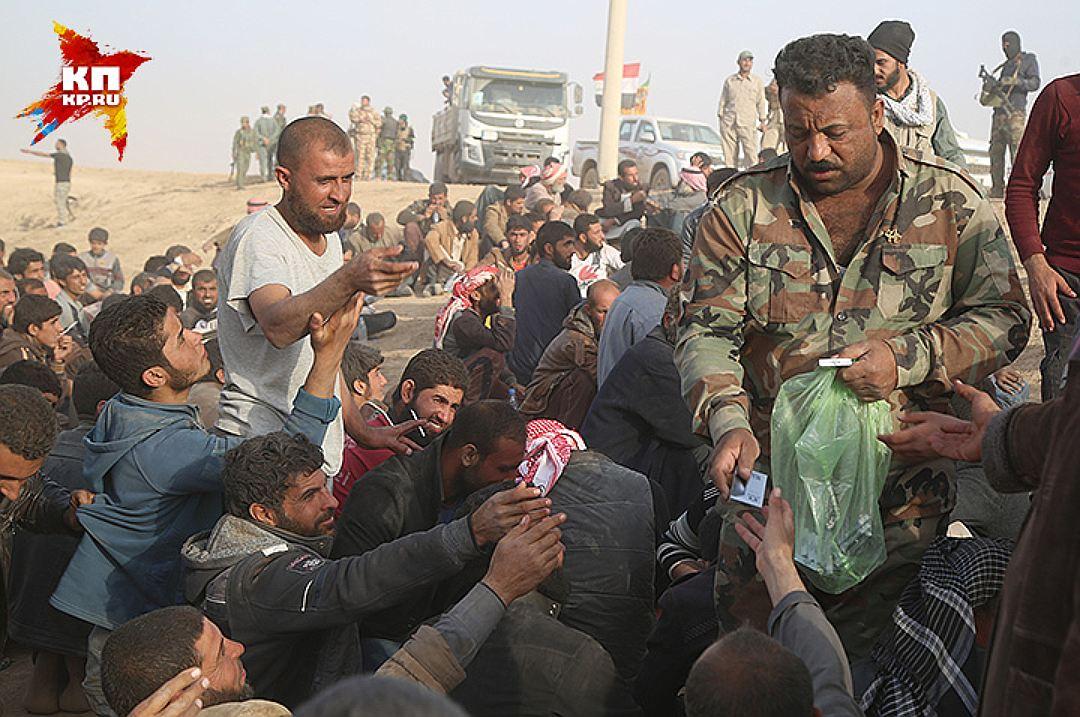 Иракский офицер раздает сигареты. Фото: Александр КОЦ, Дмитрий СТЕШИН