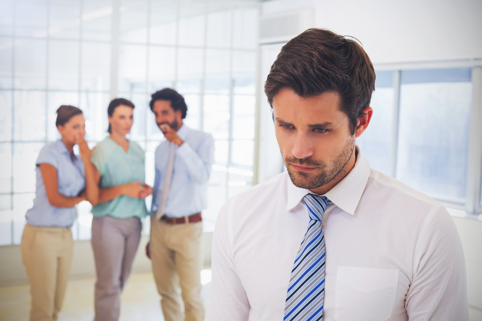 A man standing in front of coworkers whispering about him