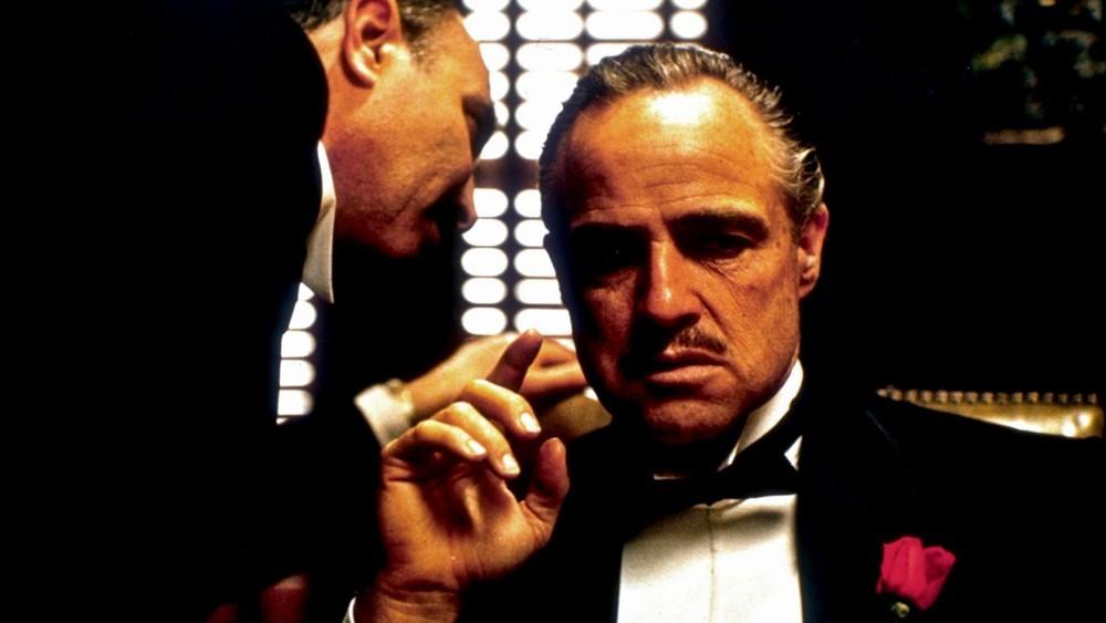 Homem falando no ouvido de outro homem de terno em uma cena de uma das indicações de filmes.
