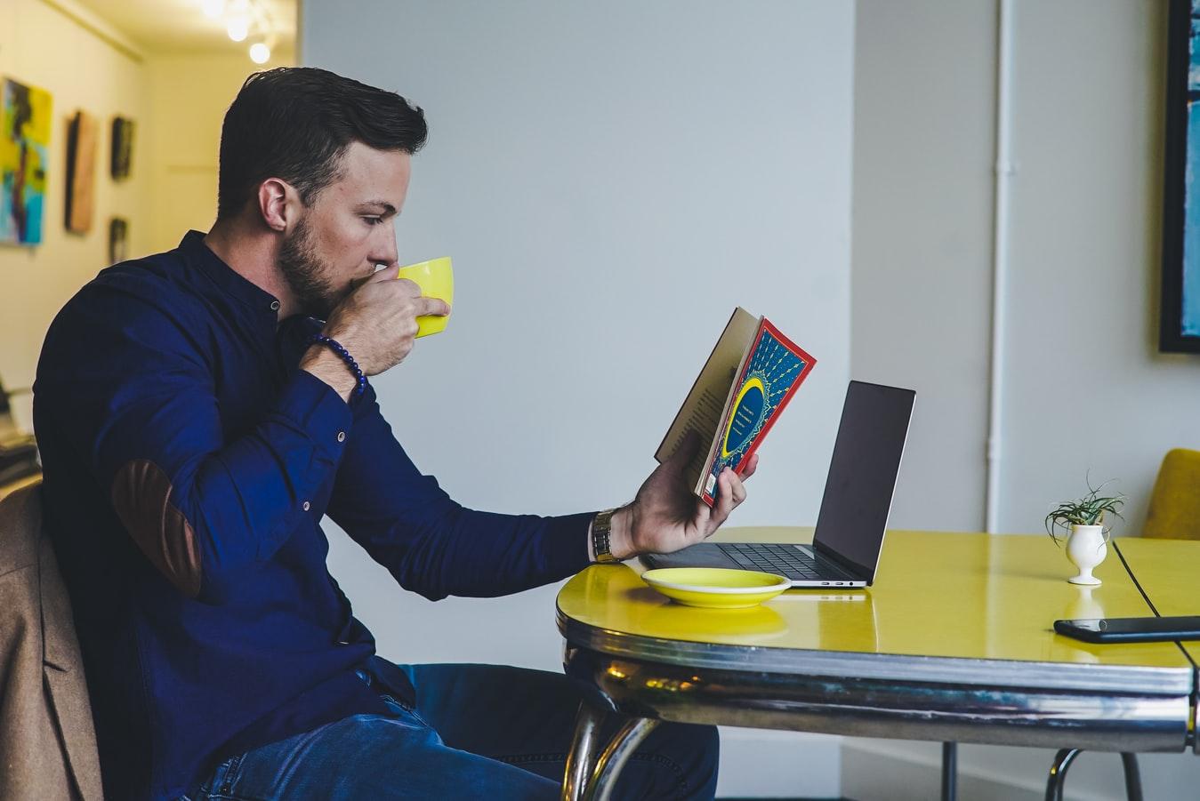 Homem lendo e tomando café
