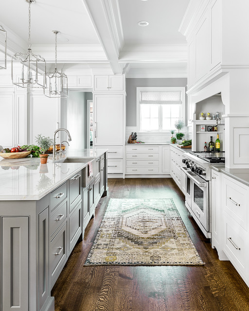 traditional grey and white kitchen with shaker cabinets, wood floors, white countertops, large center island and silver pendant lighting