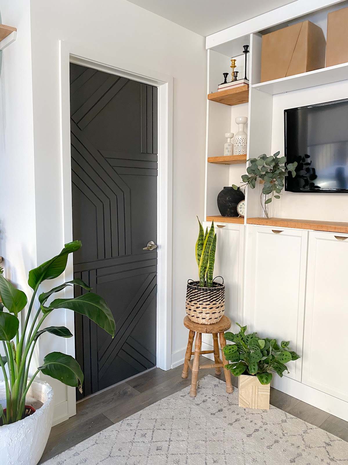 Black Modern barn door in under $30. White Ikea build in entertainment centre beside the door