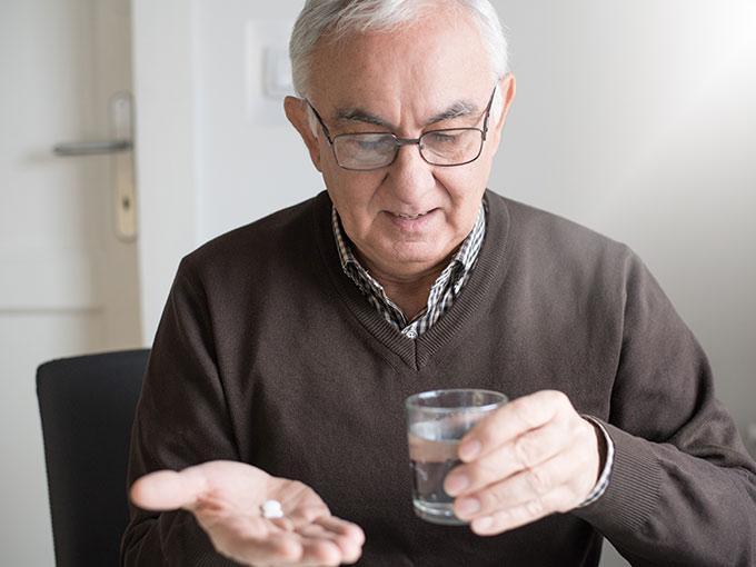 Älterer Mann nimmt seine Antidiabetika mit einem Glas Wasser ein.