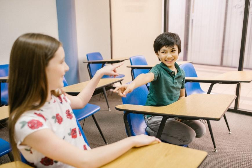A boy and a girl having fun in a new classroom.