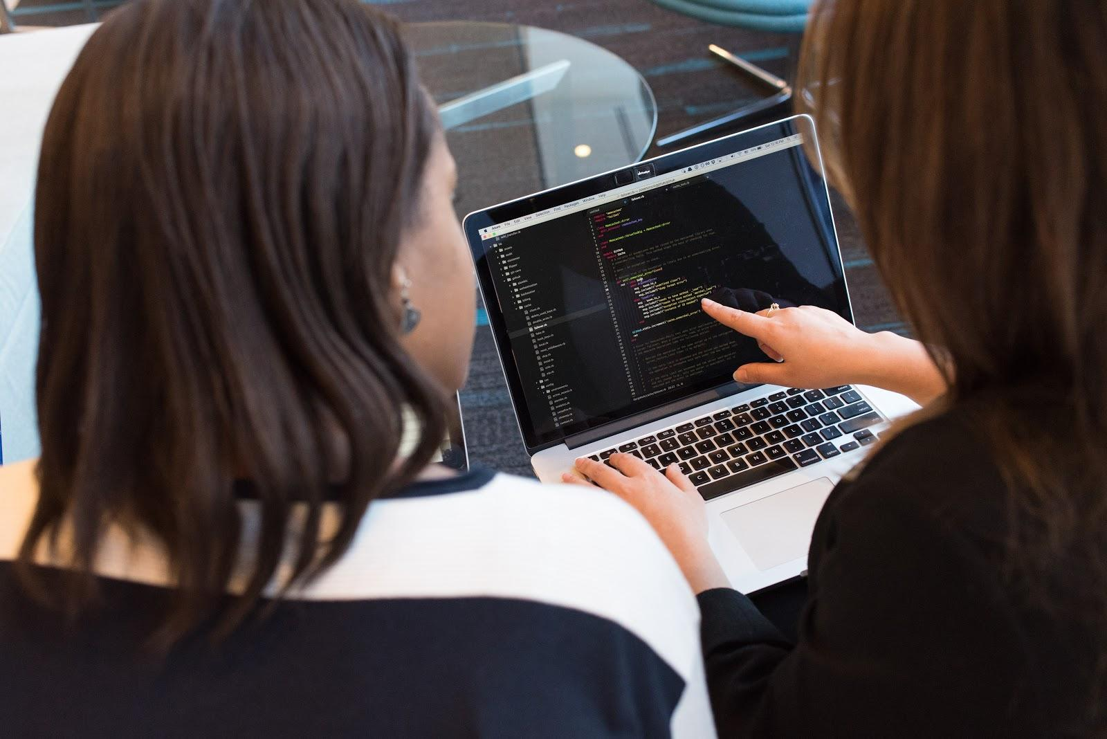 Two women looking at the code at a laptop