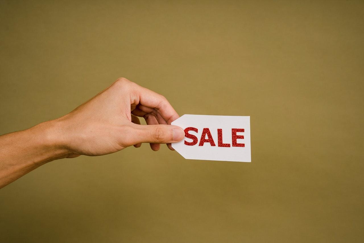 Osoba (ręka) trzymająca etykietę sprzedaży na musztardowym tle