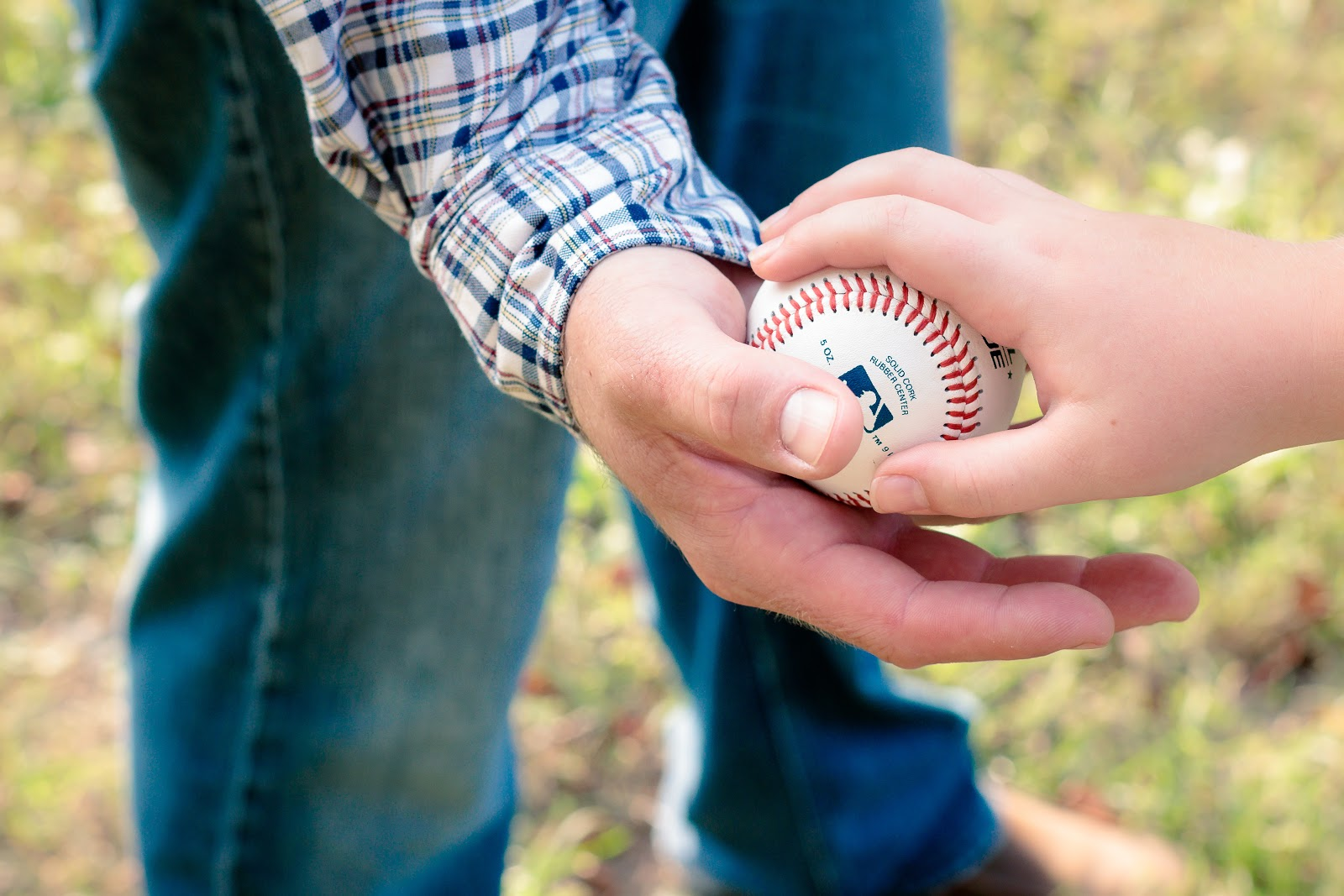 son hands a ball to father