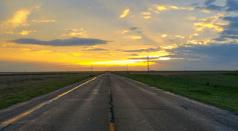 sunset in the distance on a road that goes on for miles with no traffic in sight