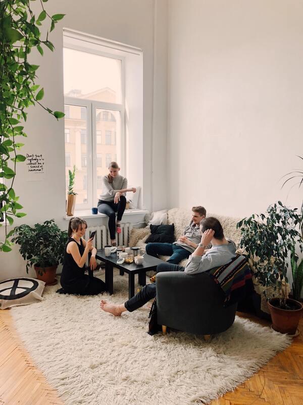 Foto tirada de todo um ambiente, com um grupo de amigos sentados na sala e conversando